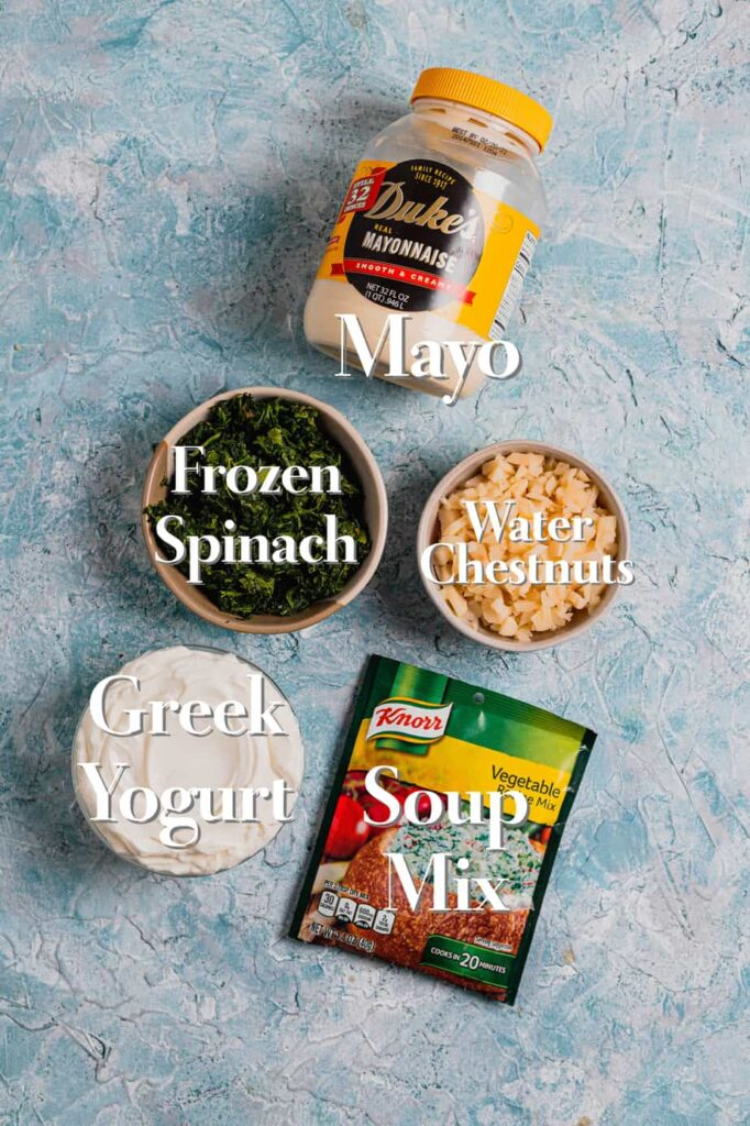 The five ingredients needed for healthy spinach dip are in various bowls and containers on a blue backdrop.