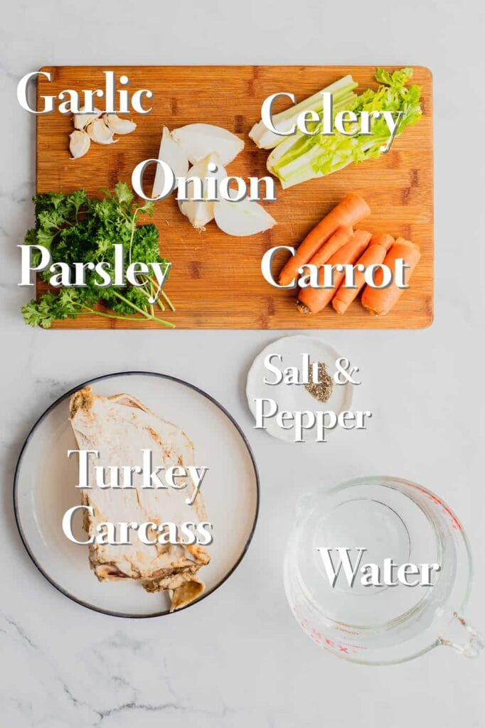 All the ingredients for easy turkey stock are on a marble backdrop. The vegetables are on a wooden cutting board, the seasoning is in a small ramekin, the turkey carcass is on a plate, and a measuring cup is filled with water.