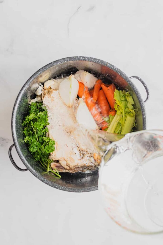 All the ingredients for homemade easy turkey stock are in a large stock pot and water is being poured over them.