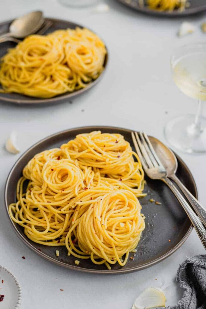 A small, dark brown plate is covered with little spirals of spaghetti aglio e olio. There is a fork and spoon resting on the plate and a glass of sparkling wine up and to the right of the plate.
