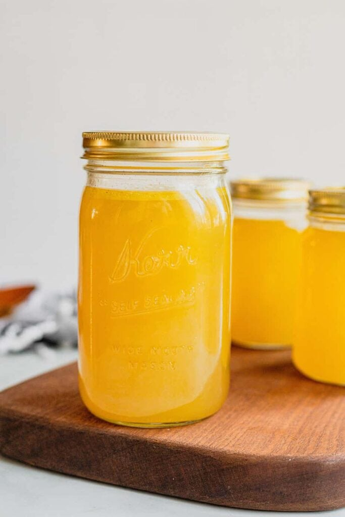 A mason jar is filled with an easy turkey stock recipe that is homemade. The jar sits on a dark brown cutting baord.