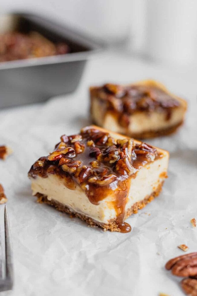A pecan pie cheesecake bar sits on a piece of parchment paper. A runny drip of pecan pie filling drips off the right hand side of the bar.