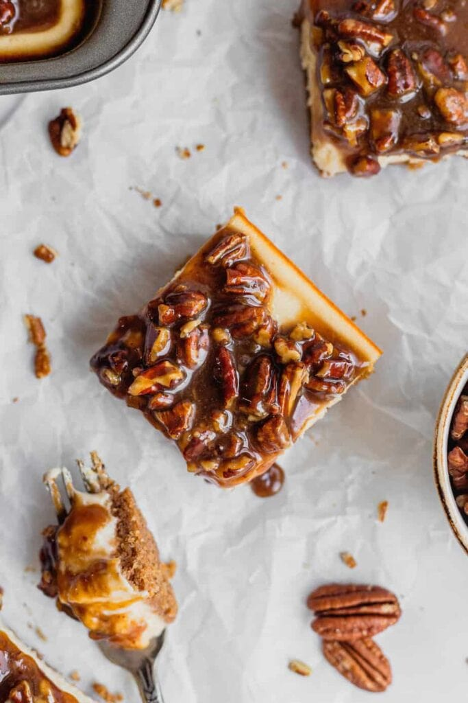 An overhead shot of a piece of pecan pie cheesecake bars. There are crumbs, pecan pieces, and other bars scattered around the parchment paper everything sits on. A fork with a bit of cheesecake bar is in the bottom left corner.
