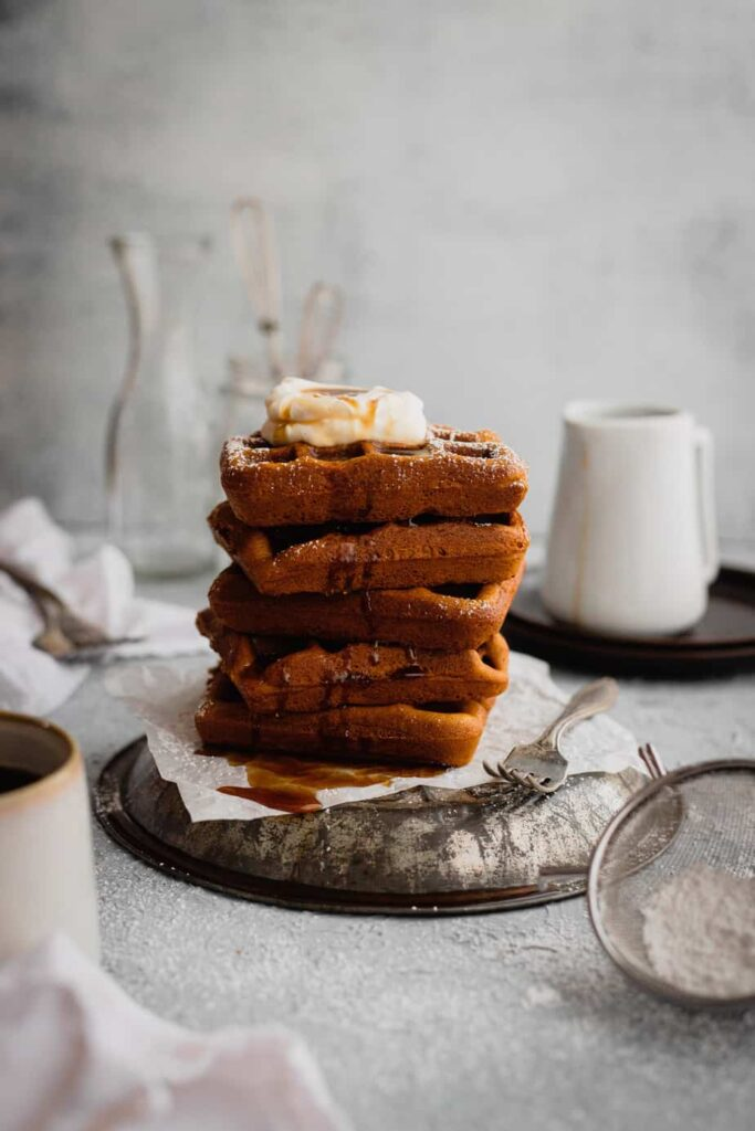 A stack of gingerbread waffles are set on an overturned antique pie plate on a piece of parchment paper. They are topped with fresh whipped cream. There is a fork next to the waffles and a white pitcher and clear glasses in the background.