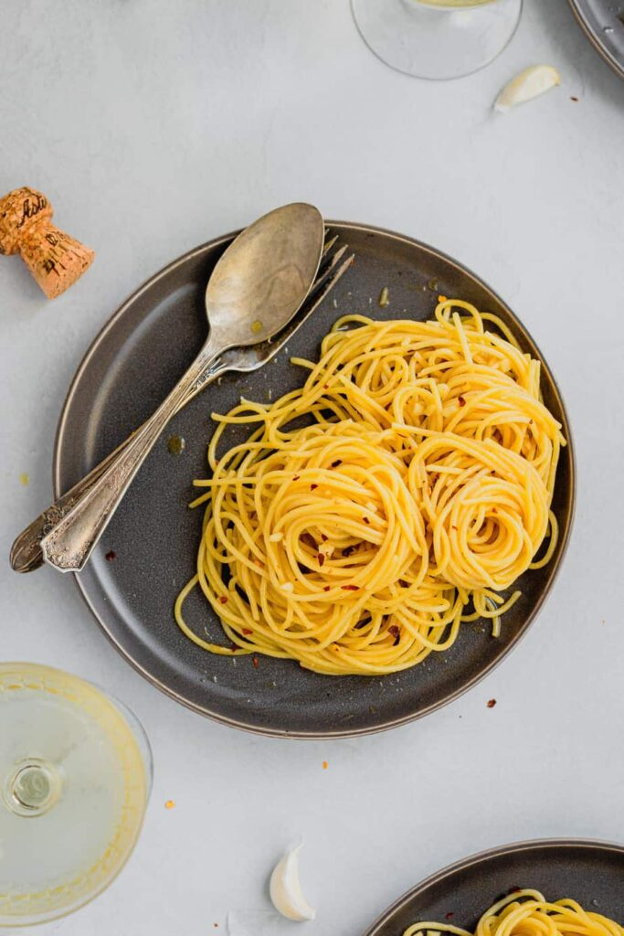A small, dark brown plate is covered with little spirals of spaghetti aglio e olio. There is a fork and spoon resting on the plate and garlic cloves and a glass of sparkling wine next to the plate.