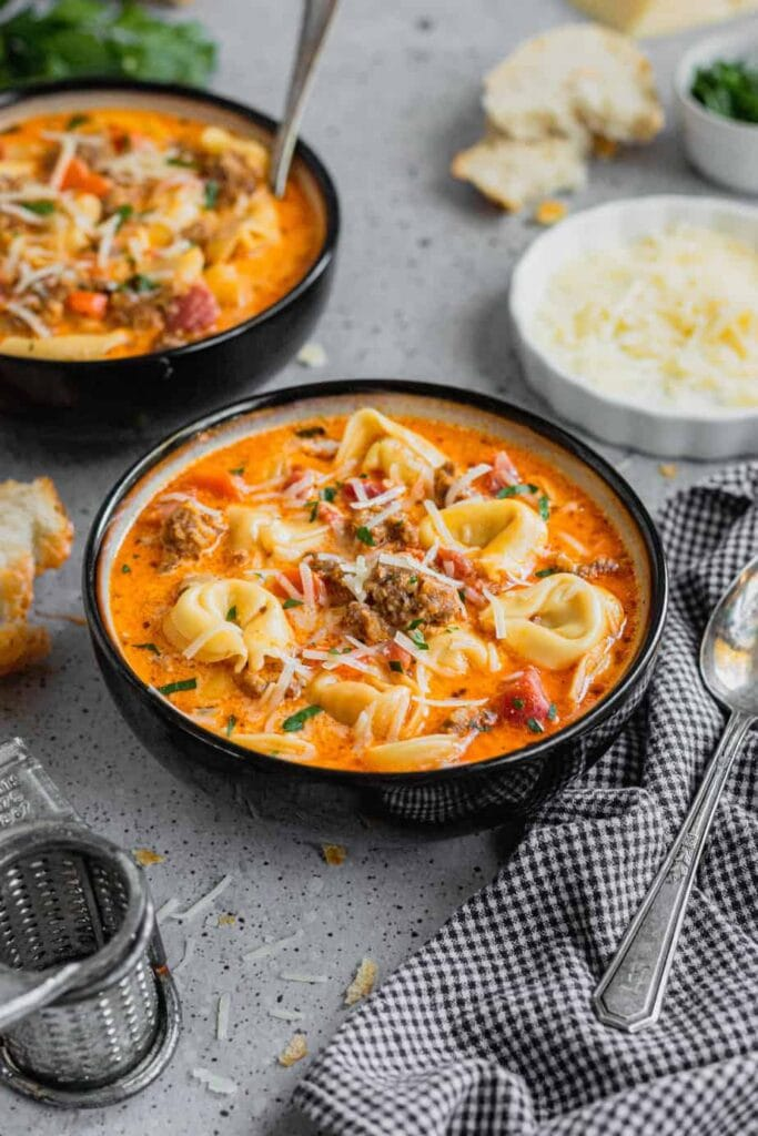 A black bowl is filled with sausage and tortellini soup. It is garnished with parmesan and parsley. The bowl sits in front of another bowl of soup on a gray speckled backdrop.