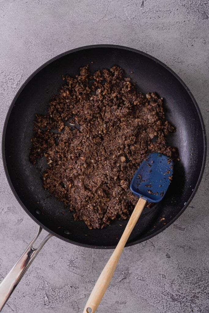A sauté pan is filled with cooked duxelles. There is a blue rubber spatula in the pan.