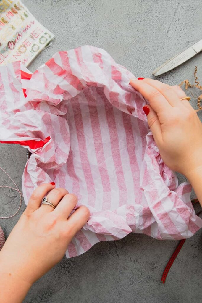 Hands line a cookie tin with red and white striped tissue paper for mailing cookies.