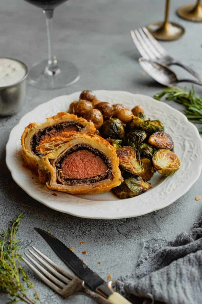 Slices of deer wellington are on a white plate with roasted potatoes and brussels sprouts.