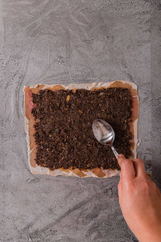 A hand pushes the back of a spoon to spread cooked duxelles onto the layer of prosciutto.