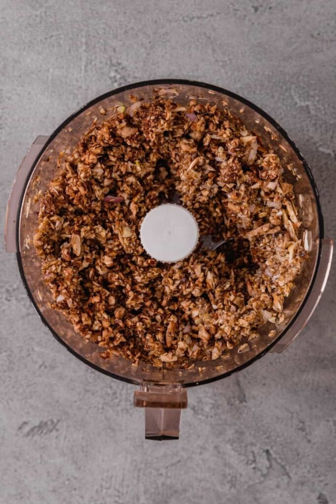 The bowl of a food processor is filled with an uncooked duxelles mixture.