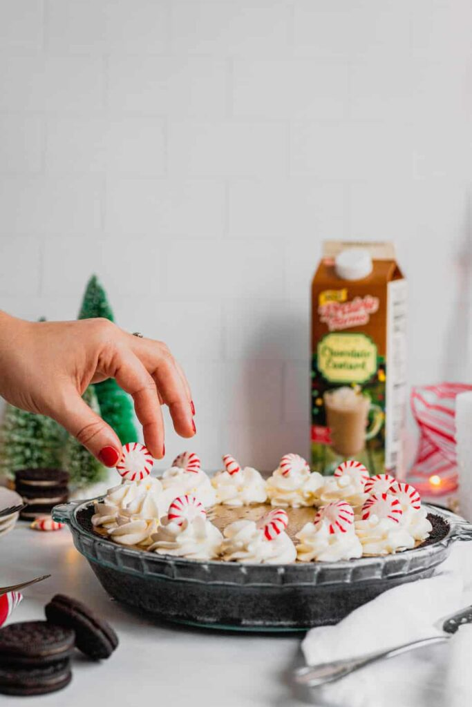 A hand reaches out to garnish a dollop of whipped cream on a peppermint mocha cream pie.