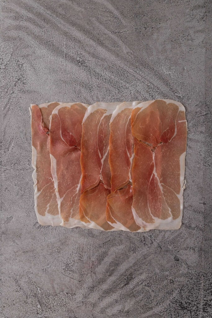 A rectangle of layer prosciutto on a piece of plastic wrap.