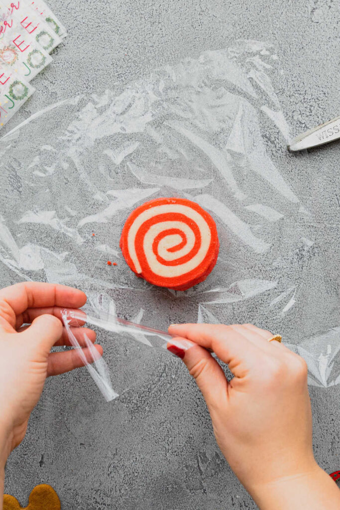 Hands wrap a piece of plastic wrap around peppermint pinwheel cookies.