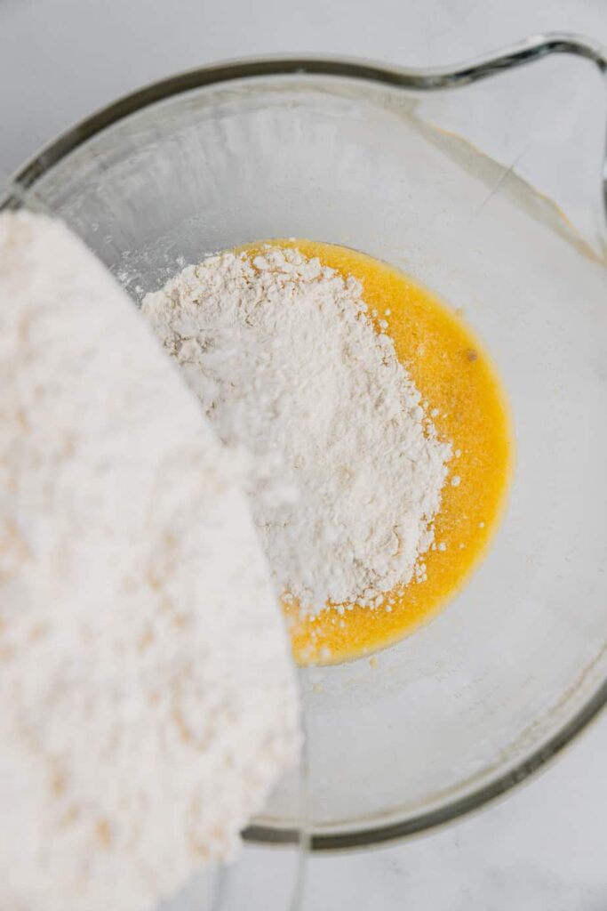 Flour is added to the wet ingredients in a glass mixing bowl.