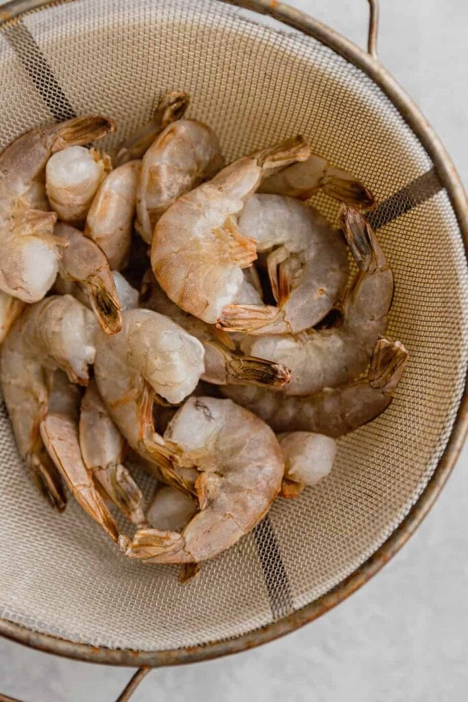 A colander set over a mixing bowl is filling with raw shrimp.