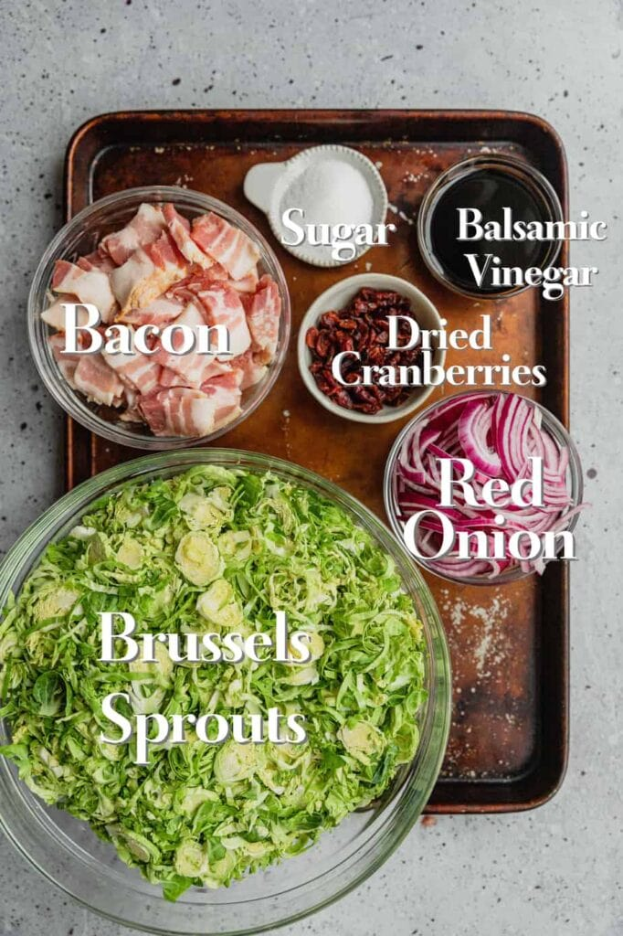 All of the ingredients for bacon braised Brussels sprouts are laid out on a baking tray in various glass bowls.