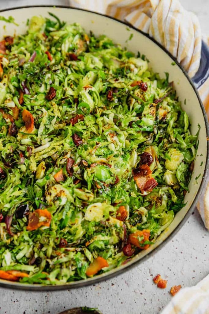 A shallow Dutch oven is filled with shaved bacon braised Brussels sprouts drizzeled with balsamic reduction.