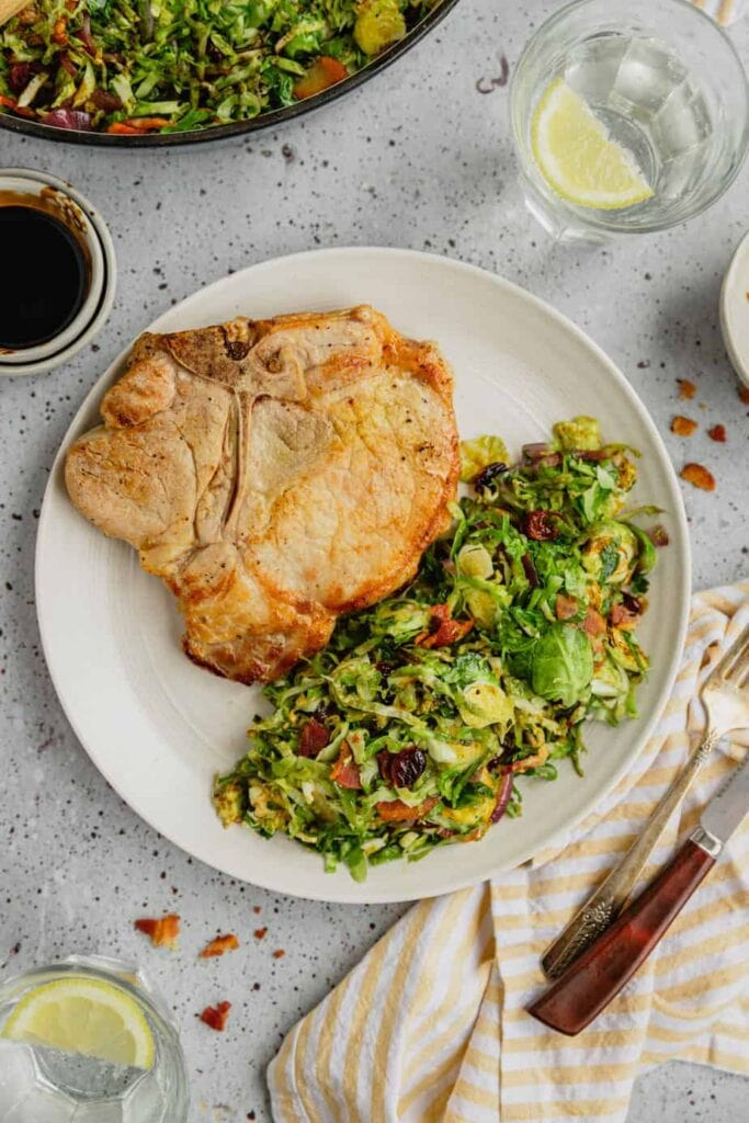 An off-white plate filled with bacon braised Brussels sprouts with balsamic reduction and cranberries. They are served alongside a bone-in pork chop.