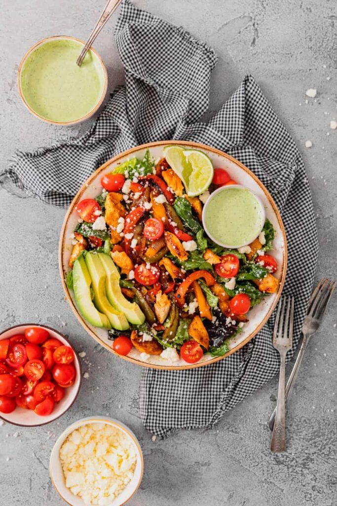 An overhead shot of a large bowl filled with chicken fajita salad ingredients on a grey backdrop. It is surrounded by ingredients in small bowls and extra salad dressing.
