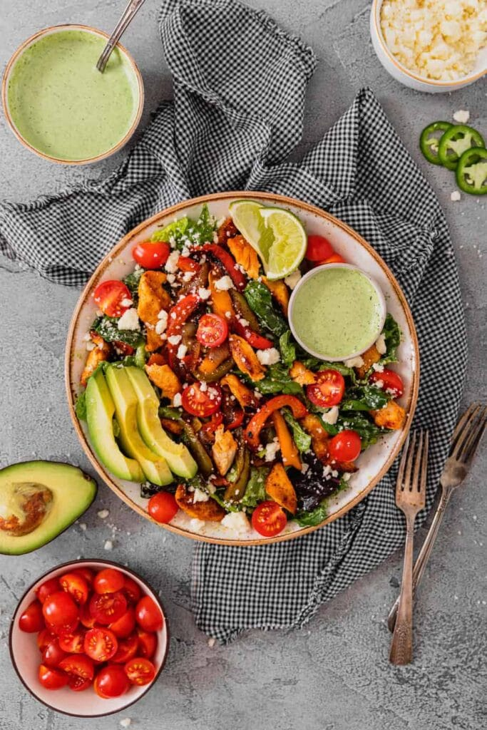 An overhead shot of a large bowl filled with chicken fajita salad ingredients on a grey backdrop. It is surrounded by ingredients in small bowls.