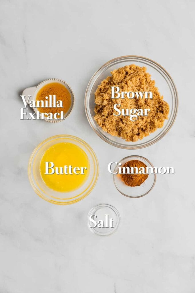 The ingredients for cinnamon roll filling are in various bowls and measuring cups on a white marble backdrop.