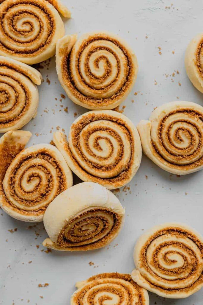 Cut, unbaked cinnamon rolls are scattered on a white marble work surface.