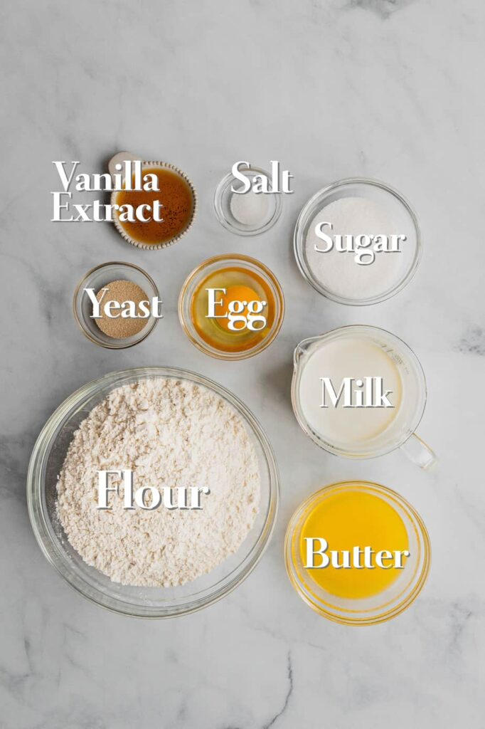 All the ingredients for an enriched cinnamon roll dough are on a white marble backdrop.