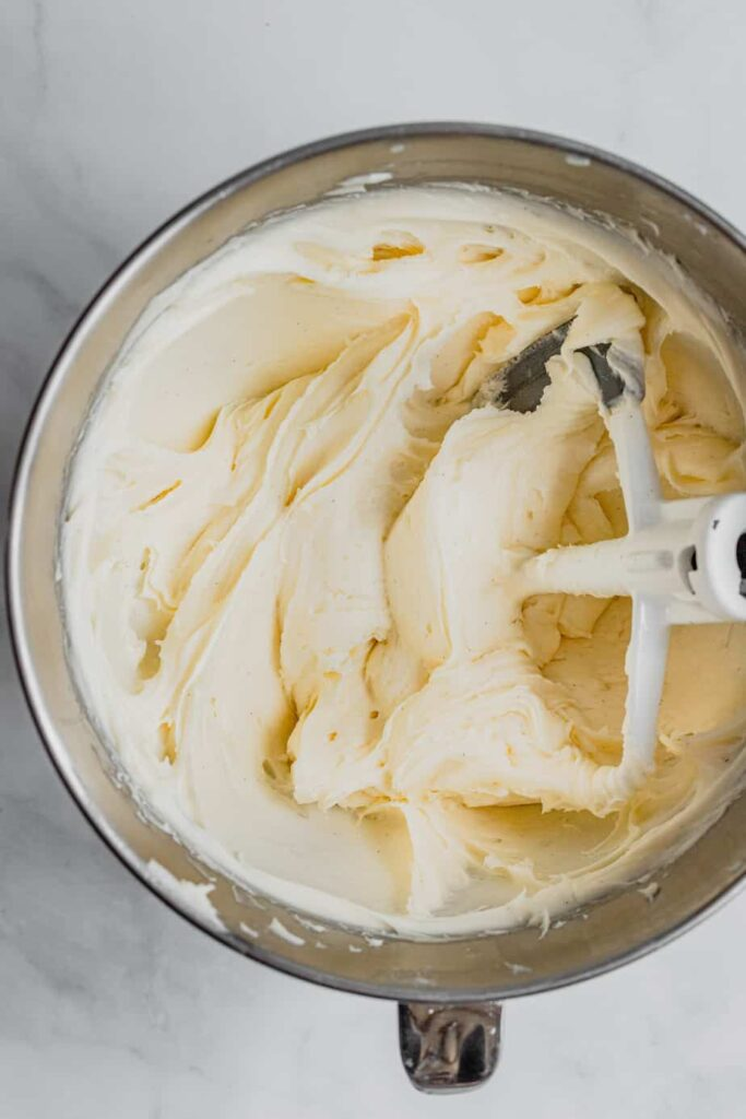 A stainless steel mixing bowl filled with cream cheese frosting.