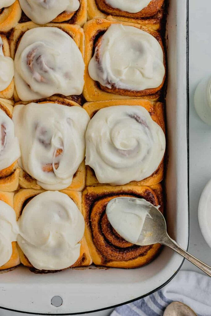 A batch of overnight cinnamon rolls recipe covered in cream cheese frosting.