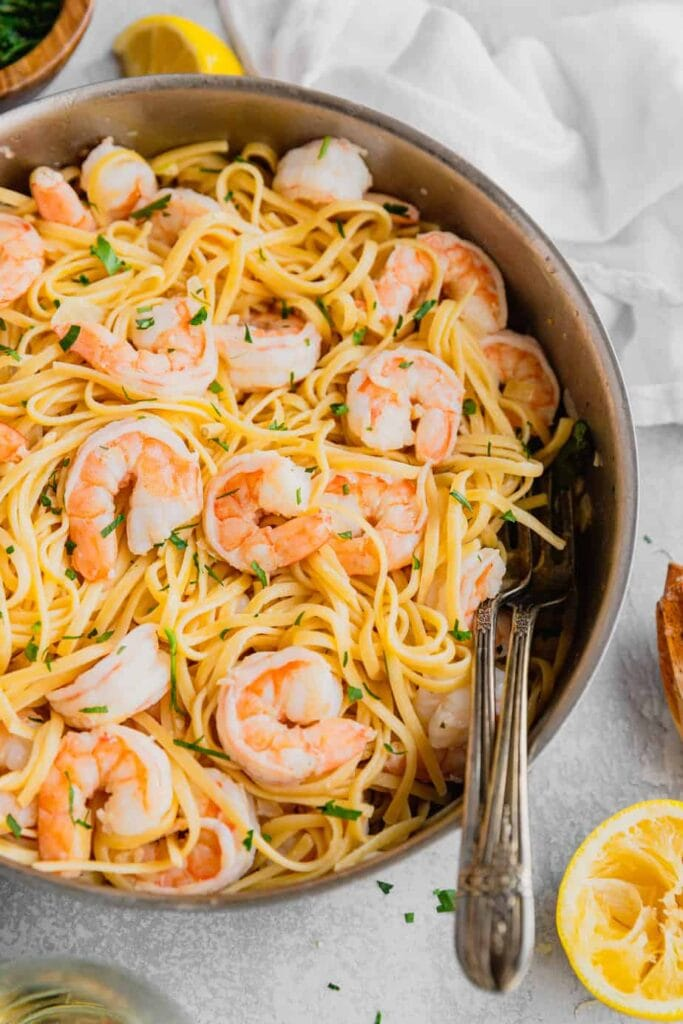 A skillet filled with easy shrimp scampi linguine. There are two serving forks in the skillet and fresh lemon and parsley on the edges of the picture.