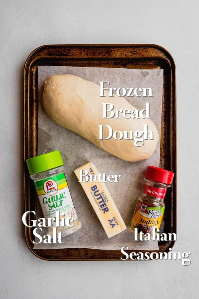 All of the ingredients for homemade garlic bread are on a parchment lined baking sheet.