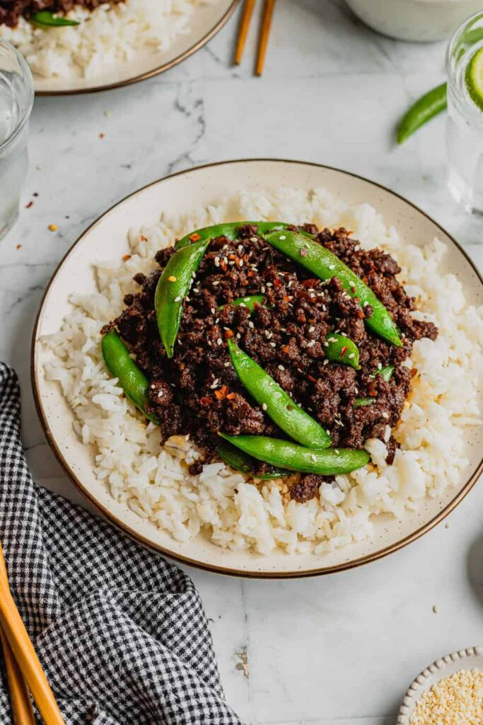 A plate is filled with white rice and topped with spicy Korean-inspired venison made from ground venison. The dish is garnished with snap peas, sesame seeds, and crushed red pepper flakes.