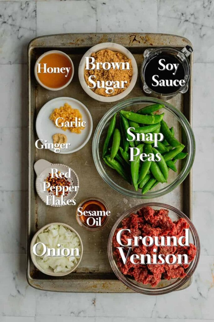 All of the ingredients for spicy Korean-style venison are in various glass measuring cups and bowls on a baking tray.
