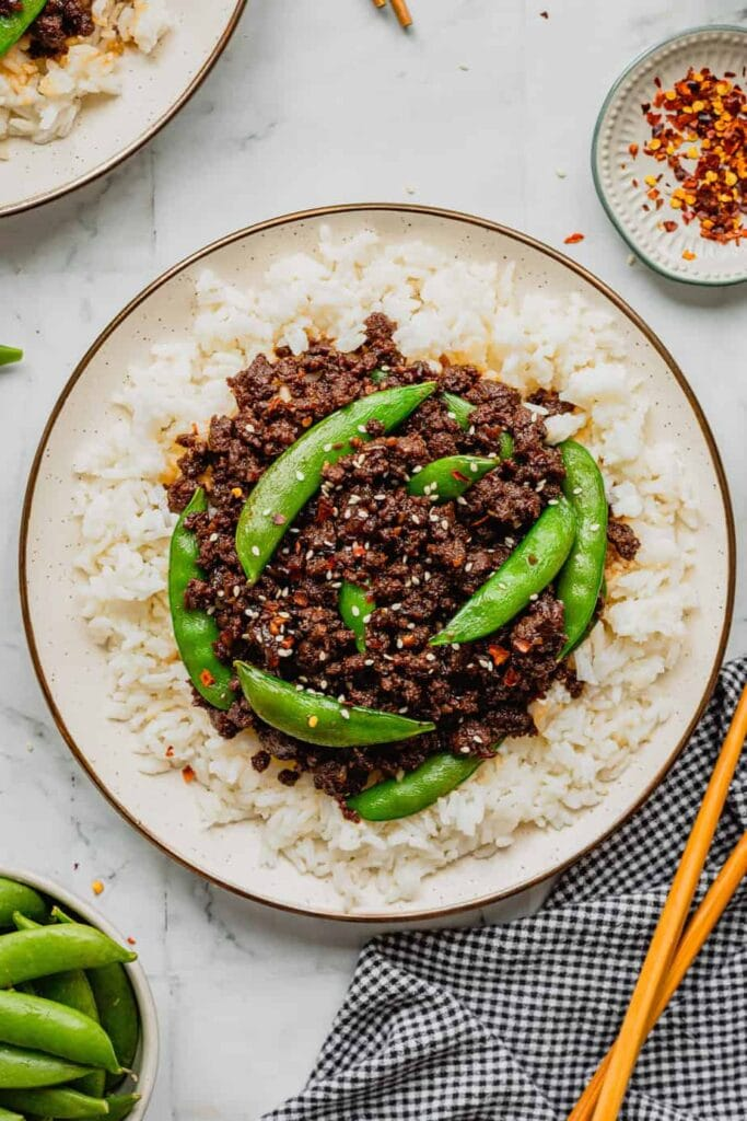 A dish filled with rice is topped with spicy Korean-inspired venison and snap peas. There is a small dish of red pepper flakes in the upper right hand corner and chopsticks in the bottom right.