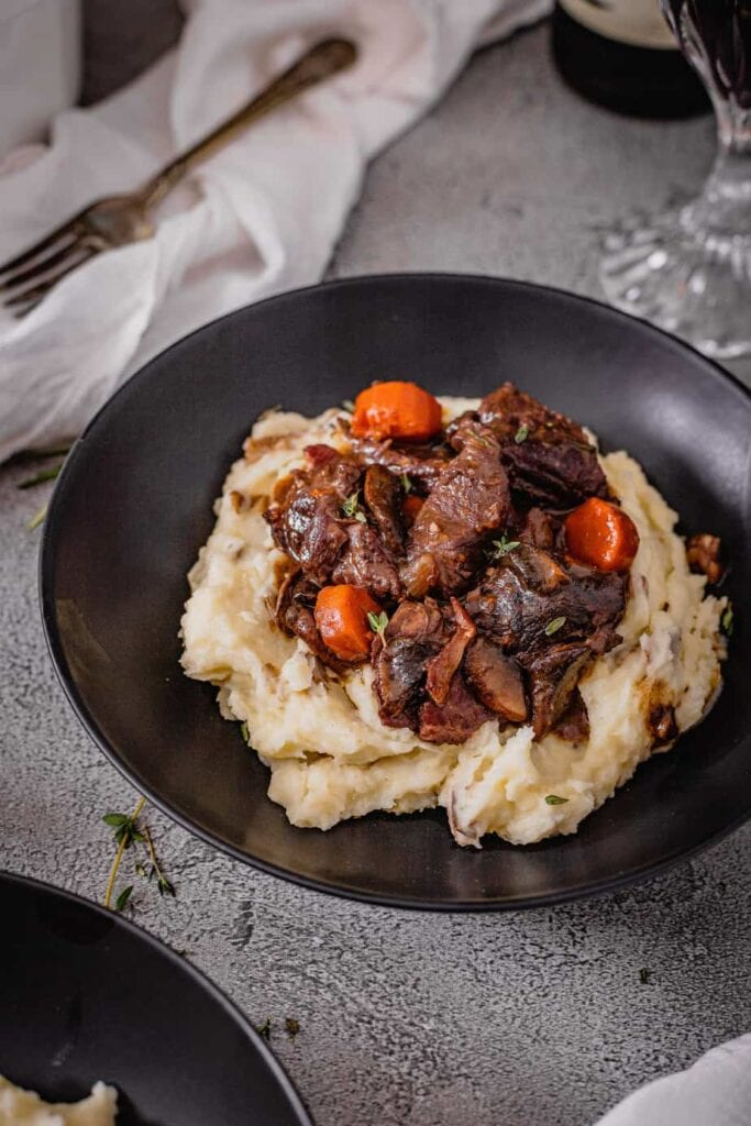 A black bowl is filled with mashed potatoes and topped with red wine venison stew. The bowl sits on a grey backdrop and there is a white napkin and wine glass in the background.