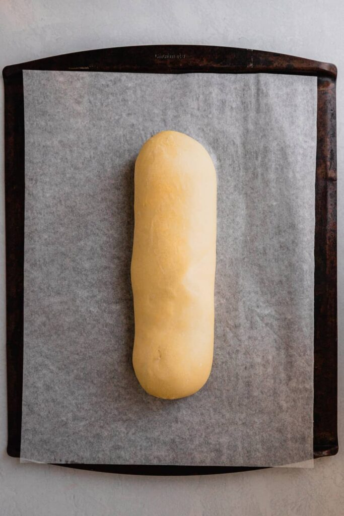 A loaf of risen bread dough on a parchment lined baking sheet.