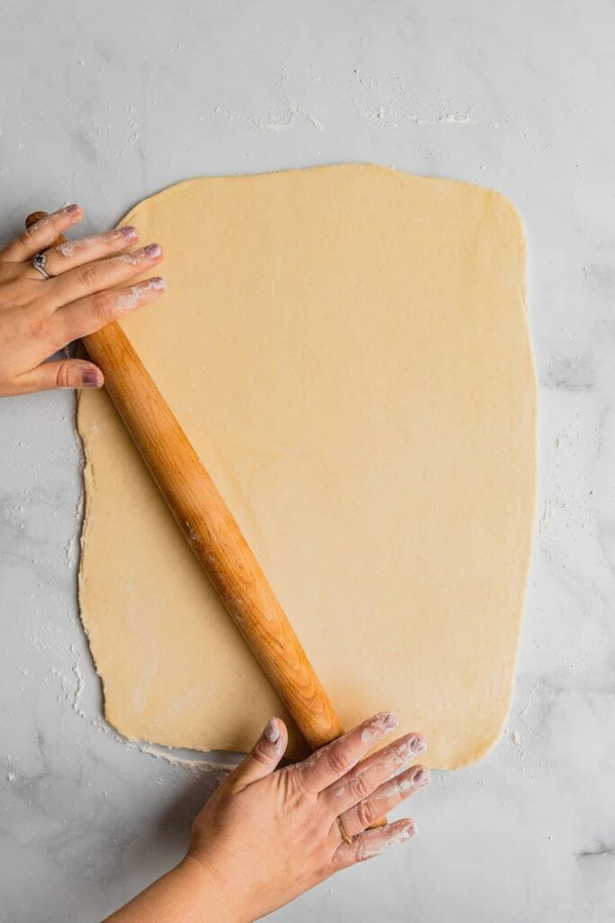 A woman rolls out the dough for an overnight cinnamon rolls recipe on a floured marble surface.