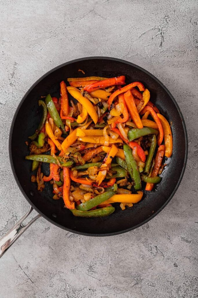 Peppers and onions in a skillet.