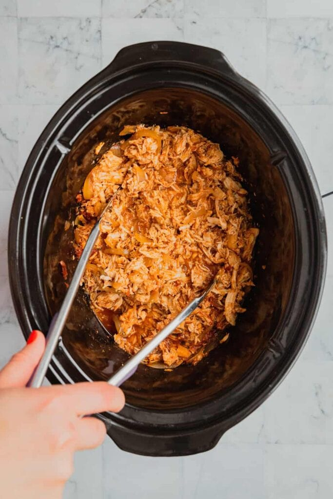 A hand holds tongs that are shredding slow cooker salsa chicken.