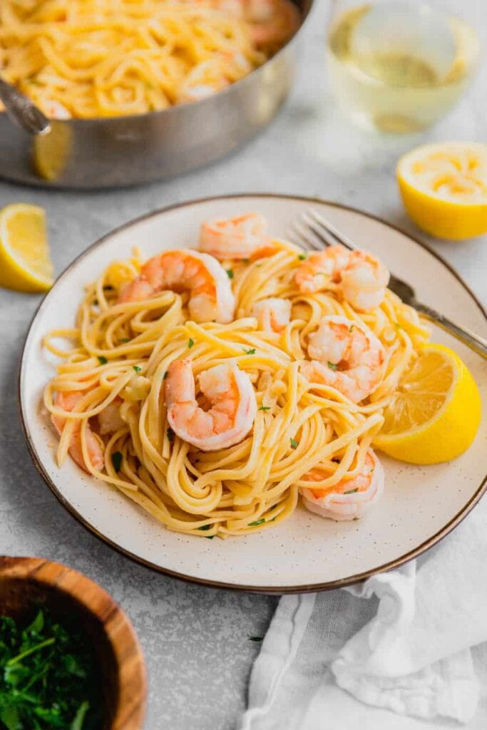 A white plate filled with a serving of easy shrimp scampi linguine and a lemon wedge for garnish.