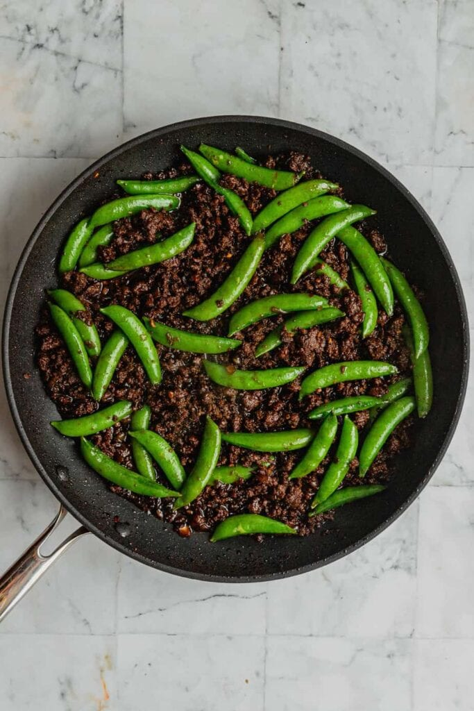 Spicy Korean-inspired venison and snap peas are in a large skillet.
