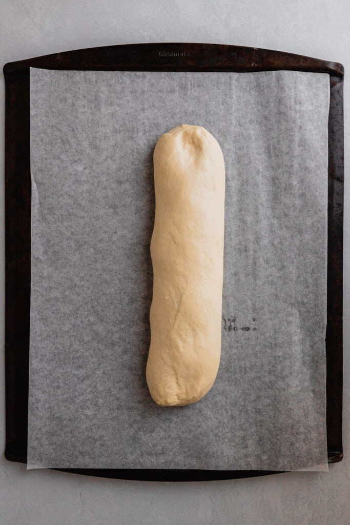 Bread dough on a parchment lined baking sheet.