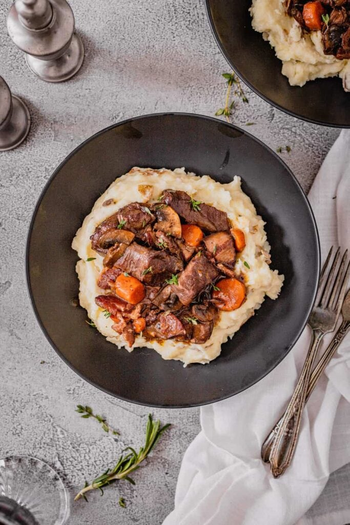 An overhead view of a black bowl filled with red wine venison stew that is on top of mashed potatoes.