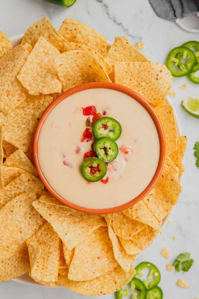 A white bowl with an orange rim is filled with homemade white cheese queso and is surrounded by tortilla chips.