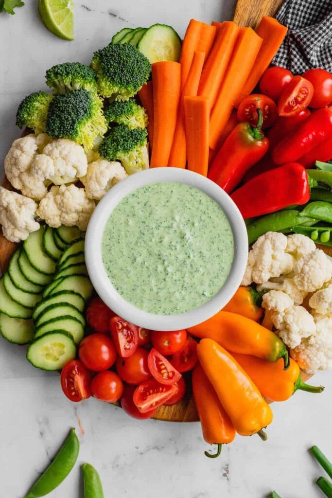 A small white bowl filled with green goddess dip sits on a wooden platters surrounded by an assortment of fresh vegetables.