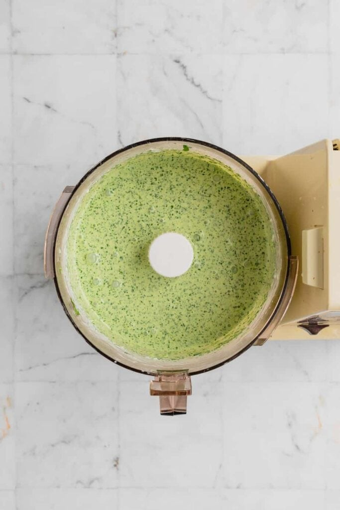 A food processor bowl full of the blended and smooth green goddess dip.
