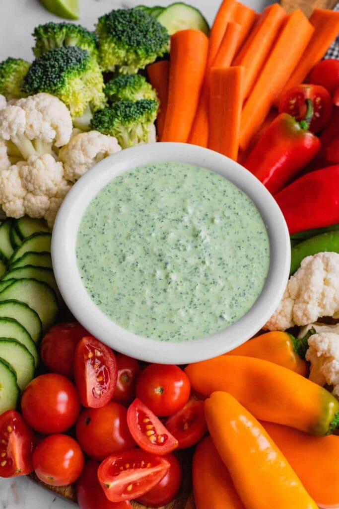 A small white bowl full of green goddess dip surrounded by fresh vegetables.