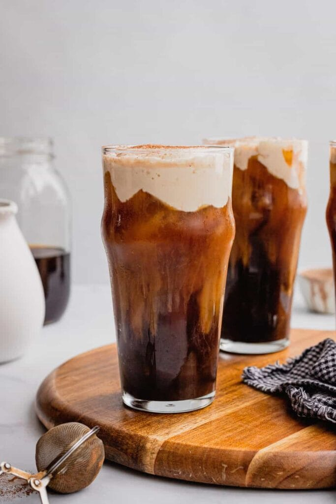 A glass filled with Irish Cream Cold Foam recipe sits on a wooden serving tray. There are more filled glasses in the background.