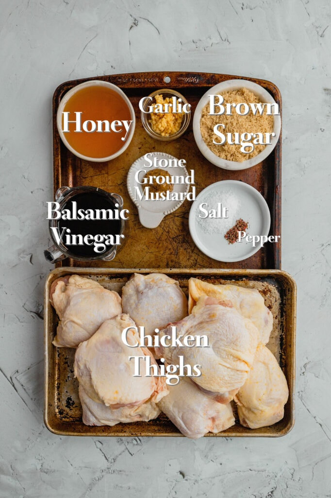All of the ingredients for honey balsamic chicken are on a baking sheet in various glass measuring cups and bowls.